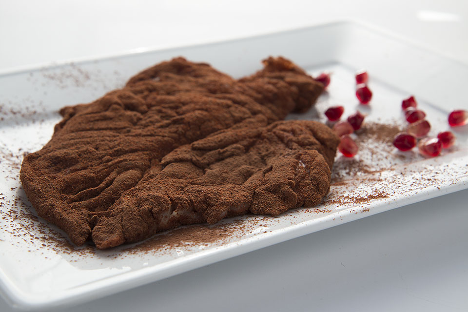 Chicken coated with cocoa powder and paprika